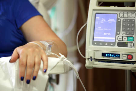 Infusion pump feeding IV drip into patients arm focus on needle Stock Photo - 24913937