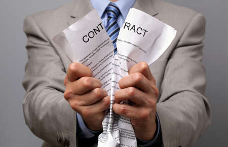 Angry businessman tearing up a document, contract or agreement photo