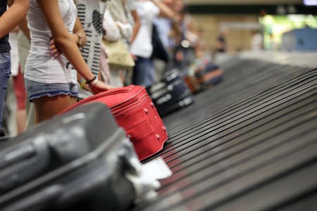 luggage airport: Suitcase on luggage conveyor belt in the baggage claim at airport