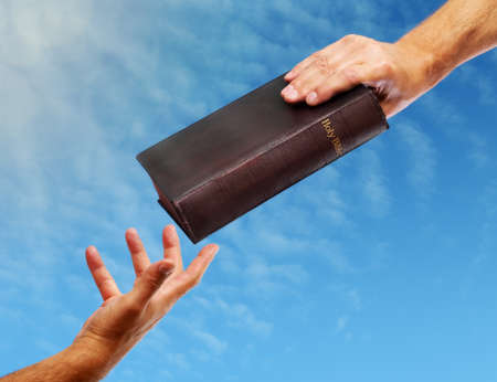 worshipper: Passing over the bible hand giving a bible to another reaching out