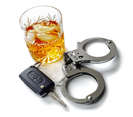 Whiskey with car keys and handcuffs concept for drinking and driving photo