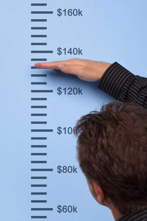 Businessman measuring dollar growth on a wall height chart photo