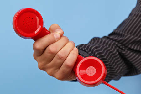 important phone call: Red phone over blue background concept for customer support line or important call Stock Photo