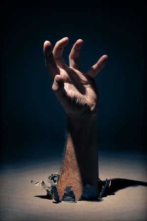 Hand coming through a hole clawing or reaching out for help - concept for mental illness or assistance photo