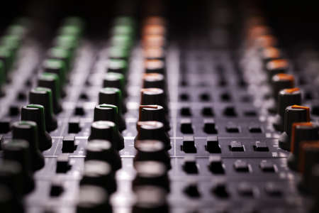 music production: Recording studio audio mixing console looking across the control knobs