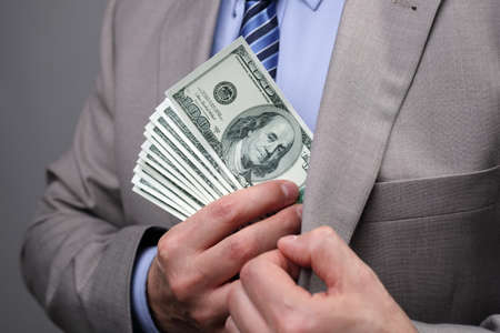 bribing: Man putting money in suit jacket pocket concept for corruption, bribing, paying or business wealth Stock Photo