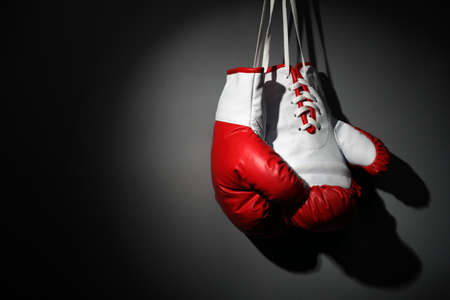 hang up: Boxing gloves hanging on wall low key gray background with copy space