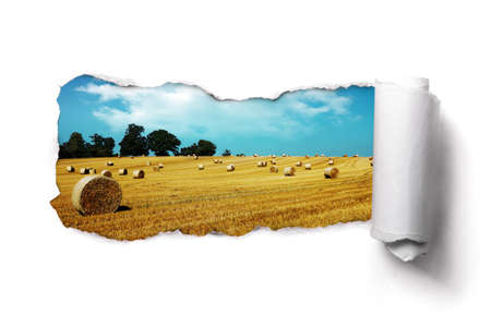 Tearing a paper frame hole to reveal hay bale field landscape Stock Photo