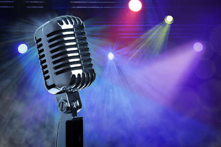 vocals: Retro microphone with stage lighting background
