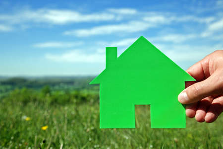 home planning: Real estate housing development concept hand holding green house symbol in a field