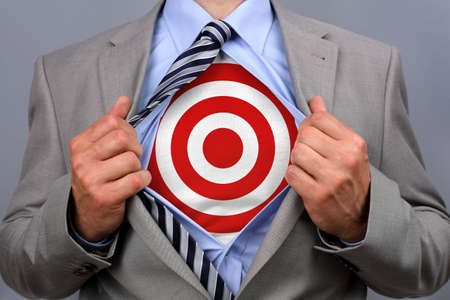 target business: Businessman in classic superman pose tearing his shirt open to reveal target symbol on chest concept for human resources and recruitment