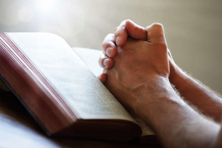 prayer: Hands folded in prayer on a Holy Bible in church concept for faith, spirtuality and religion Stock Photo