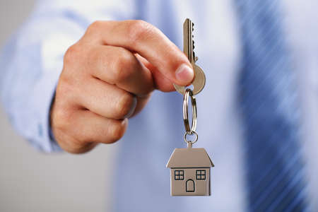 Holding out house keys on a  house shaped keychain Stock Photo
