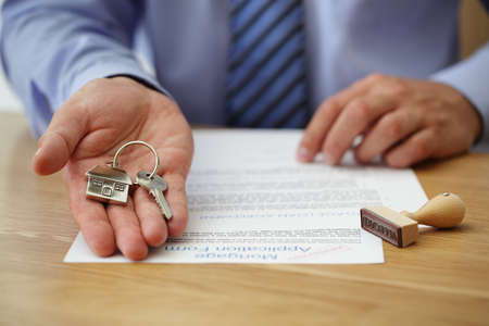 Makelaar huis sleutels overhandigen met erkende hypotheek aanvraagformulier Stockfoto