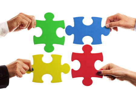 Teamwork strategy or partnership concept with business team holding jigsaw pieces together photo