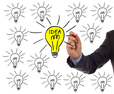 Businessman drawing a light bulb on a whiteboard concept for bright idea and inspiration photo