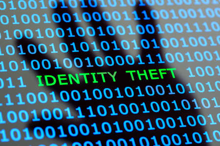 theft: Internet identity theft on a digital tablet with reflection of hackers hand concept for online digital crime