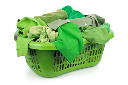Green clothes in a laundry basket on white background concept for environmental conservation and eco friendly washing photo