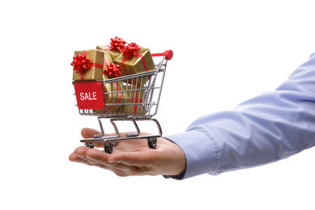Shopping cart full of gold gift boxes and red sale sign photo