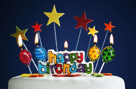 gateau anniversaire: Des bougies et des ballons de joyeux anniversaire br�le sur un g�teau Banque d'images