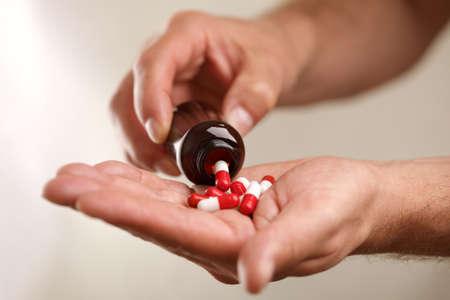 medecine: Verser capsules à partir d'une bouteille de pilules dans la main Banque d'images