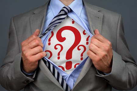 changing form: Businessman in classic superman pose tearing his shirt open to reveal question mark symbol on chest concept for human resources and recruitment