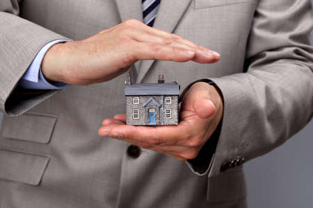 Businessman protecting a model house, real estate or insurance concept photo