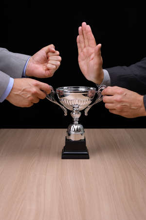 rivalry: Business rivalry and confrontation at work, two businessmen fighting over a silver trophy
