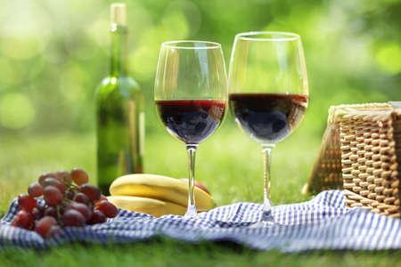 hamper: Picnic setting with red wine glasses bottle and picnic hamper basket  Stock Photo
