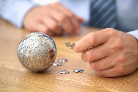 Zakenman oplossen wereldbol puzzel concept voor zakelijke oplossingen en strategie