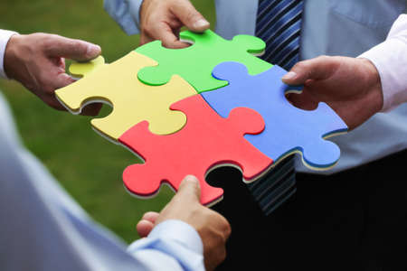business relationship: Teamwork concept four business people holding jigsaw puzzle pieces together