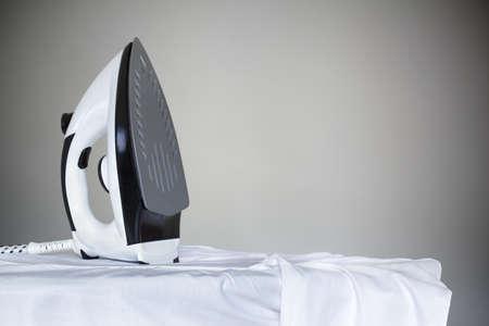 Strijken een wit shirt met een stoomstrijkijzer op een strijkplank