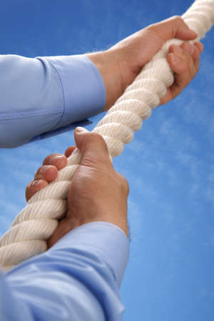 risk of war: Climbing a rope upwards towards a blue sky concept for aspirations, growth and leadership Stock Photo