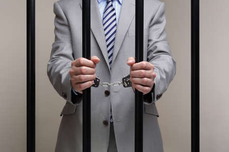 capital punishment: Businessman behind bars in prison concept for white collar crime