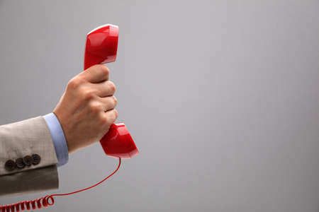 customer support: Red phone over gray background concept for customer support line or important call