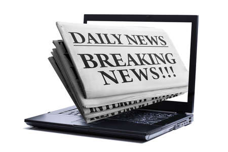 breaking news: Newspaper through a laptop screen  concept for latest online news