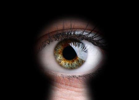 Womans Auge späht durch ein Schlüsselloch Konzept für Neugier, Stalker, Überwachung und Sicherheit