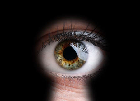 big brother spy: Womans eye peeking through a keyhole concept for curiosity, stalker, surveillance and security