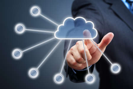 Businessmans hand pressing cloud icon on visual touch screen concept for cloud computing photo