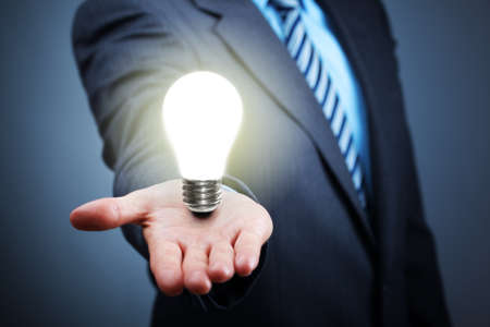 inventor: Businessman with illuminated light bulb balancing on his hand concept for idea, innovation and inspiration