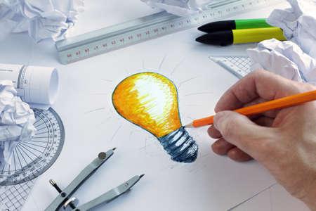 Diseñador que drena una bombilla, el concepto de intercambio de ideas y la inspiración
