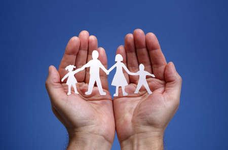proteccion: Recorte el papel de la cadena de la familia con la protección de las manos ahuecadas, el concepto de la seguridad y el cuidado