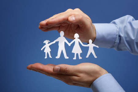 child protection: Cutout paper chain family with the protection of cupped hands, concept for security and care Stock Photo