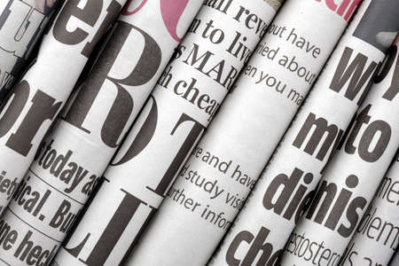 articles: Newspaper headlines shown side on in a stack of daily newspapers
