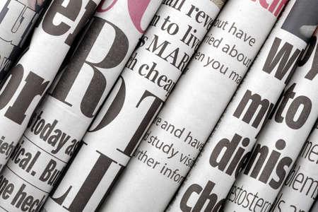 Titoli dei giornali illustrati lato su di una pila di quotidiani