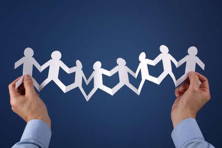 recursos humanos: Concepto de trabajo en equipo con el grupo de cadena de papel de personas de la mano celebradas sobre fondo azul