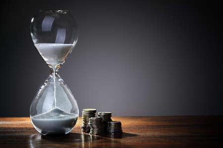 締め切り時間であり、砂時計と英国コイン通貨とお金の概念 写真素材