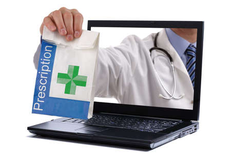 Internet drug store concept doctor holding prescription medicine through a laptop screen photo
