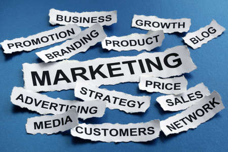 headline: Marketing concept torn newspaper headlines reading marketing, strategy, branding, advertising etc