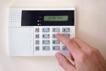home security system: Security alarm keypad with person arming the system